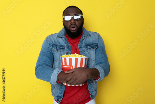 Fotografie, Obraz  Waist up of surprised African guy holding bucket with popcorn