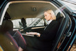 attractive blonde woman using laptop while sitting in car