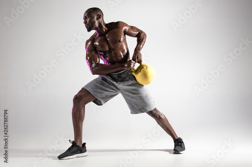 Young african-american bodybuilder training over grey background Принти на полотні