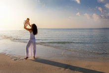 Happy Mother Holds Her Baby Girl Up In The Air On A Beach During Sunset Time