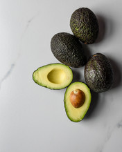 Close Up Of Avocados With One Cut In Half On A White Countertop.