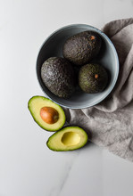 Bowl Of Avocados With One Cut In Half On A White Countertop.