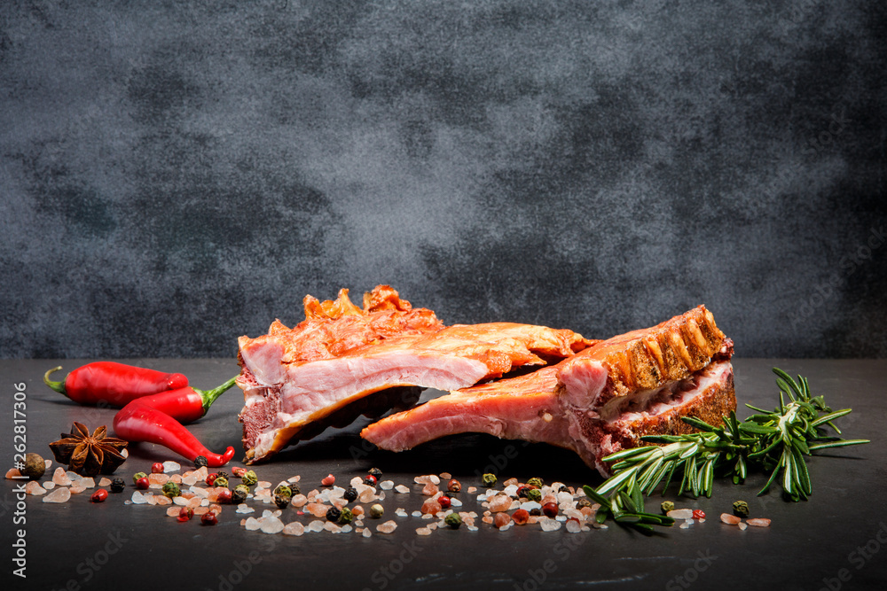 Fototapety, obrazy: big pieces of smoked ribs with spices, rosemary and two chili peppers