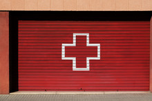 Cross On Red Garage Door Of Emergency Ambulance On Sunny Day On City Street