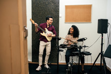 Cheerful Man Playing Guitar And Woman Playing Drums