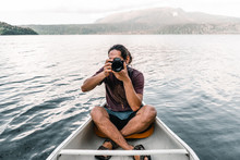Young Photographer With Camera In Boat Floating Between Water Surface Near Coast With Green Trees