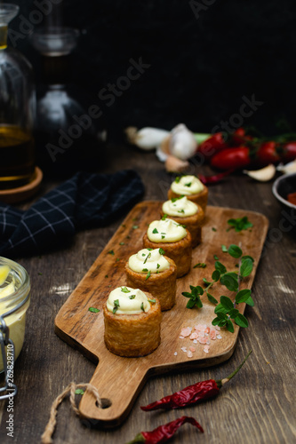Photo Gourmet dish, spanish appetizer - patatas bravas served on wooden cutting board