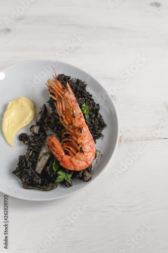 Canvas Print Black rice with seafood, shrimps, aioli served with glass of white wine, gourmet