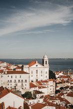 Amazing Drone View Of Blue Sky Over Tiled Roofs Of Old Houses And Calm Sea In Lisbon, Portugal