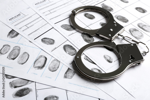 Foto Handcuffs and fingerprint record sheets, closeup