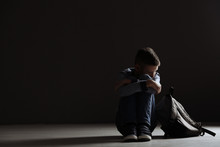 Upset Boy With Backpack Sitting In Dark Room. Space For Text