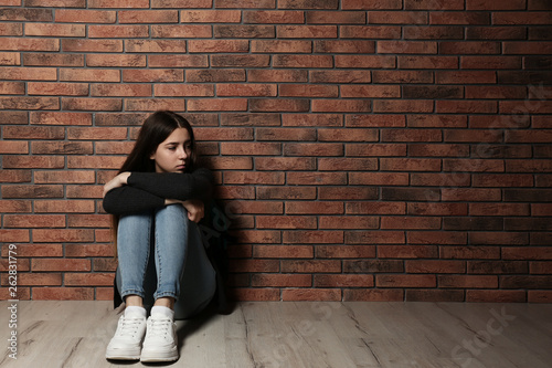 Fotomural  Upset teenage girl sitting on floor near wall. Space for text