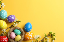 Flat Lay Composition With Painted Easter Eggs And Blossoming Branches On Color Background, Space For Text