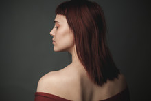 Young Woman With Red Hair In Studio. Back