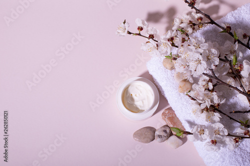 Poster Spa Beautiful Spa wellness composition with natural flower blossom, creme and towel on light pink background. Natural beauty product