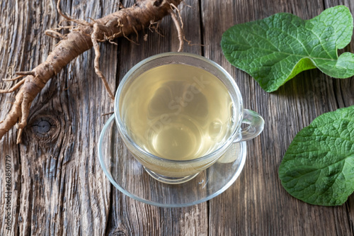 Canvas Print Burdock tea and root on a table