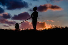 Child And Dog At Sunset