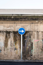 Road Sign Showing Direction Against Grunge Wall