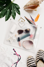 Summer Vacation Accessories And Keepsakes Packed In And Around A Clear Travel Bag