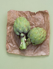 Two Globe Artichokes On Brown Paper And Green Background