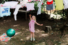 Little Girl Playing With Laundry On Laundry Line