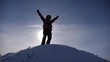 traveler rejoices in his victory at the top of a snowy hill, jumps and waves his arms, a happy man. tourist comes down from the mountains lit by the sun. Slow motion