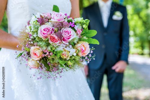 Blumenstrauß mit Brautpaar Fototapet