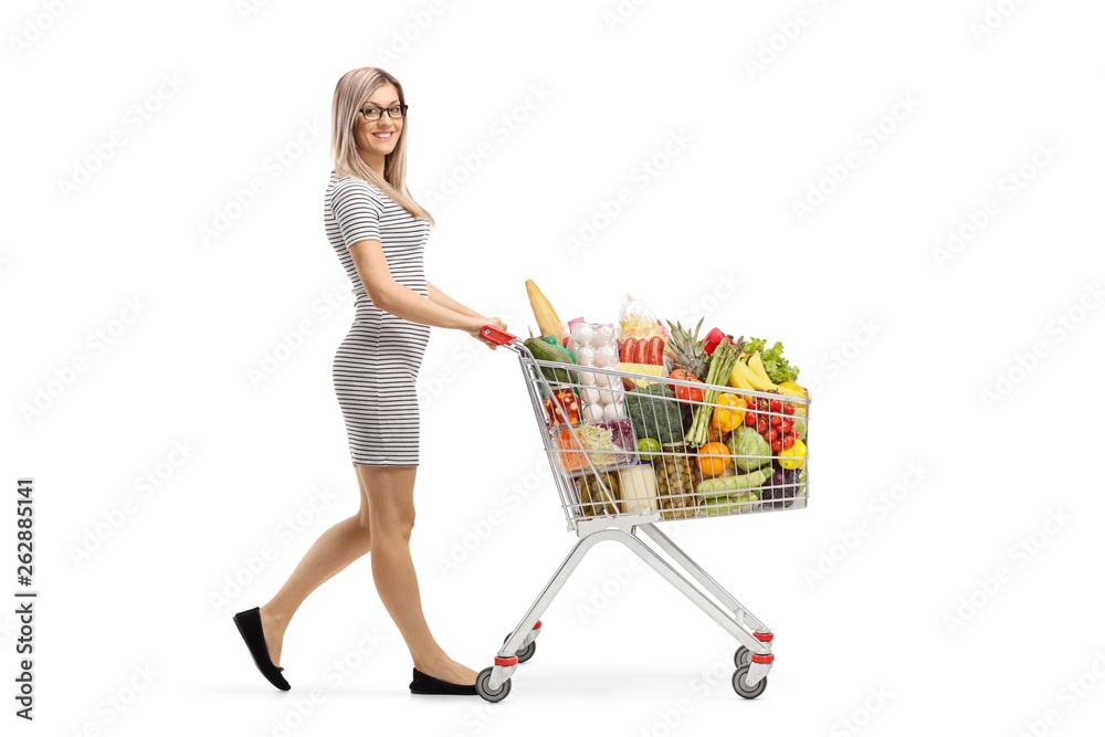 Fototapeta Full length shot of a young attractive woman pushing a shopping cart with food products and smiling at the camera