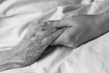 A Young Woman Holding The Hand Of An Old Woman In A Hospital Bed, Black And White