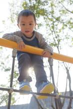 Asian Kid Climbing In Park