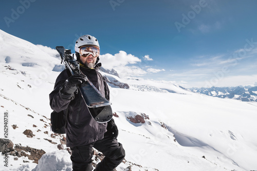 La pose en embrasure Glisse hiver Portrait bearded male skier aged against background of snow-capped Caucasus mountains. An adult man wearing ski googles mask and helmet skis on his shoulder looks mountains. Ski resort concept