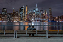 Scene Of Back Side Couple Sitting And Looking New York Cityscape Beside The East River At The Night Time, USA Downtown Skyline, Architecture And Building With Lover Concept