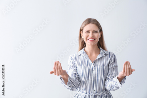 Photo  Beautiful young woman inviting viewer against light background