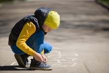 A Little Boy Tying Shoelaces After Playing Hopscotch On Asphalt Or Sidewalk. Creative Child, Fun Activity. Outdoor Games. Early Development