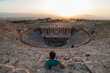 Men Sitting On The Steps Of The Ancient Amphitheater Beautiful Young Men Traveler Admiring The View. Tourist Watching On Ruins Of Theater In Ancient Hierapolis, Now Pamukkale, Turkey