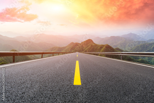 Photo sur Aluminium Jaune de seuffre Empty asphalt road and mountains with beautiful clouds at sunset