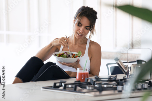Sporty young woman eating salad and drinking fruit juice in the kitchen at home Slika na platnu