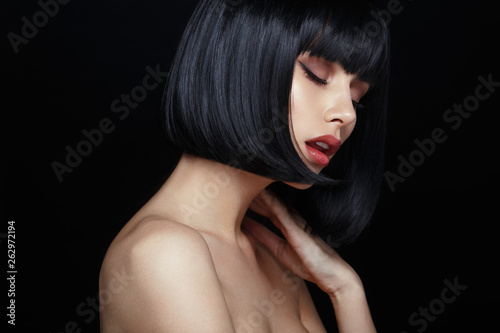 Profile portrait of a sensual young woman in black wig, bob haircuts, she touches his neck, have closed eyes, make up, big lips, naked shoulders, isolated on a black background Fotobehang