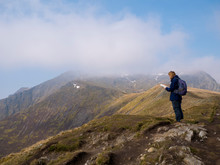 A Lone Walker Looks At A Map On The Way To The Misty Summit Of Blencathra (also Known As Saddleback) In The Lake District, Cumbria, UK With Cloud Falling Against A Blue Sky