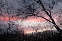 Blurry Sunset In The Rain As Seen Through A Wet Glass With Water Droplets