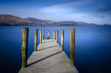 Ashness Bridge Jetty On Derwentwater In The Lake District National Park England Showing A Calm Lake And Blue Sky.