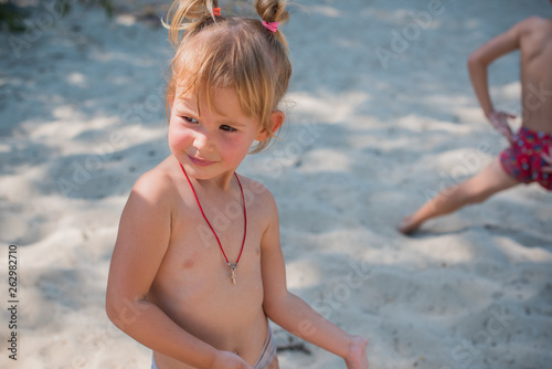 Boy and girl playing on the beach on summer holidays Canvas-taulu