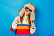A Girl With A Happy Face In A Fur Hat, Glasses And A Sweater On A Blue Background. The Concept Of Winter, Winter Holidays And Sales.
