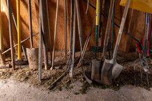 The Bottom Half Of A Selection Of Gardening Tools Including Spade, Fork, Sledge Hammer And Rake Inside A Dusty Shed, Light Coming Through The Door