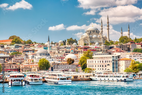 Stampa su Tela Touristic sightseeing ships in Golden Horn bay of Istanbul and view on Suleymaniye mosque with Sultanahmet district against blue sky and clouds