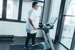 overweight tattooed man in white t-shirt running on treadmill at gym