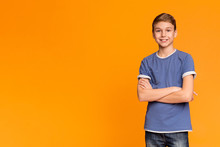 Cute Teenage Boy Posing With Folded Hands And Smiling