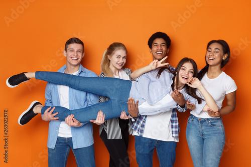 Slika na platnu Teenagers holding friend and having fun in studio