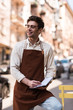 Smiling barista in glasses and apron writing in notebook on street