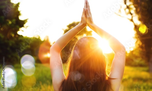 Young woman on field under sunset light doing yoga
